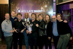 Bert Wagendorp en JW Roy met de beker. Presentator Humberto Tan van RTL Late Night tussen de winnaars. Omringd door organisatie en jury. Foto: Bastiaan Heus